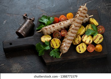 Grilled chicken skewers with fried mini potato and cherry tomatoes on a black wooden serving board, studio shot