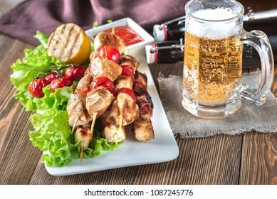 Grilled chicken skewers with mug of beer
