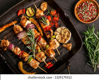 Grilled chicken skewers with spices and vegetables in a pan on a black background. Top view.