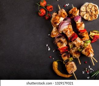 Grillte Hühnerspieße mit Gewürzen und Gemüse auf schwarzem Hintergrund. Draufsicht mit Kopienraum