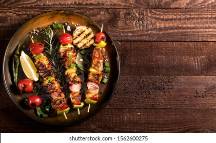 Grilled chicken skewers with spices and vegetables in a pan on a wooden background. Top view.