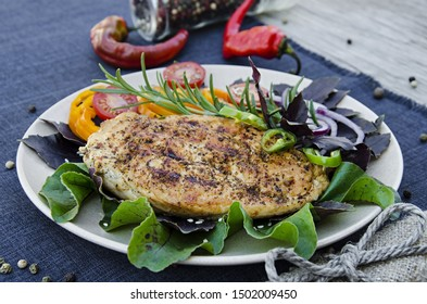 Grilled chicken steak with tomatoes, peppers, onions, rosemary and basil on a light plate. Grill menu.