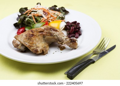 Grilled chicken steak with vegetables on white plate