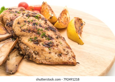 Grilled chicken steaks with vegetables on wood board isolated on white background