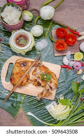Grilled chicken and sticky-rice with chili sauce on banana leaf  background - Thai traditional menu