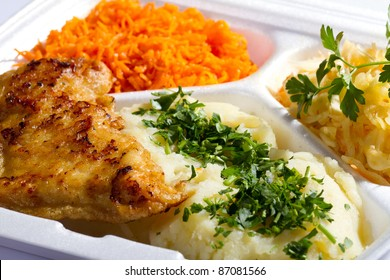 Grilled chicken in styrofoam thermal container with mashed potatoes and carrot salad