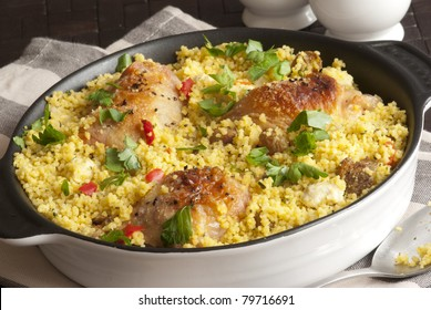 Grilled chicken thighs with Moroccan couscous and herbs in a pot