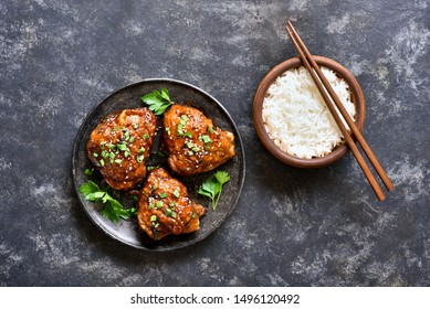 Grilled chicken thighs on plate and bowl of rice over dark stone background. Tasty food in asian style. Top view, flat lay