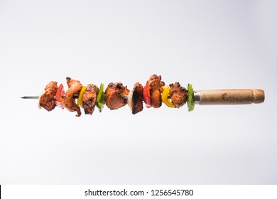 grilled chicken tikka on skewers.  served in a plate with green chutney and onion. Selective focus