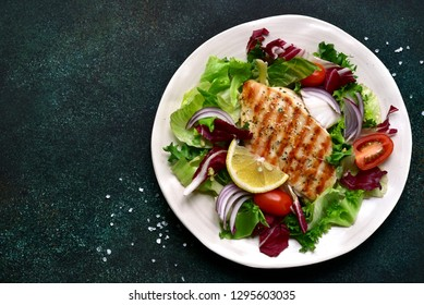Grilled chicken or turkey breast with fresh vegetable salad on a white plate over dark green slate, stone or concrete vegetable.Top view with copy space.