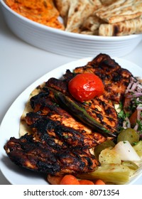 A grilled chicken in the Turkish style, with grilled tomato and chilli, pickles, chopped tomato, onion and cilantro (coriander) and a plate of different breads.