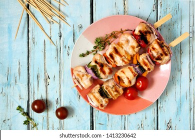 Grilled chicken and vegetable kabobs on plate. Top view over a blue wood background. Summer food concept.