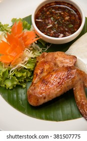 A grilled chicken wing and sticky rice
