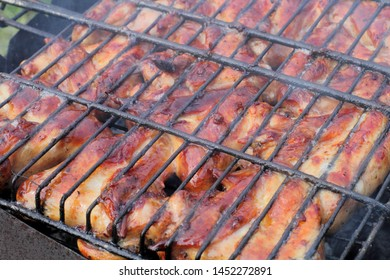 Grilled chicken wings barbecue on coals in field conditions, juicy natural color, sunny day.