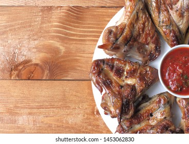 Grilled chicken wings barbecue on a white plate with tomato sauce. Background of dark wood, place for text.