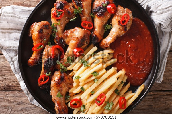 Grilled chicken wings with french fries and ketchup on the table close-up. horizontal view from above