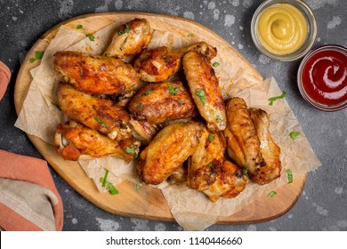 Grilled chicken wings with ketchup and mustard sauces on a wooden board. Traditional baked bbq buffalo