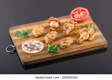 grilled chicken wings and legs on wooden plate