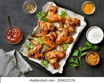 Grilled chicken wings on baking tray over dark background. Top view, flat lay