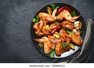 Grilled chicken wings on a black plate on a stone,concrete or slate background.Top view.