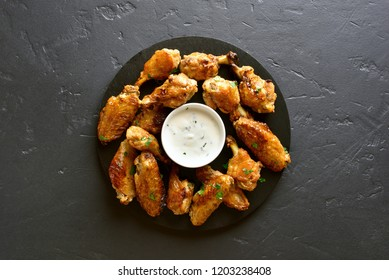 Grilled chicken wings with sauce on black stone background with copy space. Top view, flat lay