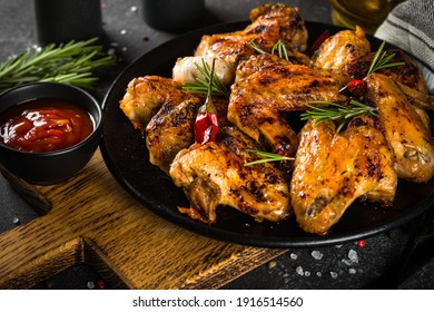 Grilled chicken wings with spices in black plate.