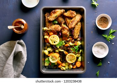 Grilled chicken wings with vegetables in baking tray. Top view, flat lay