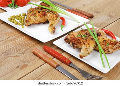 grilled chickens : grilled quarter chicken garnished with green sweet peas , and cutlery on white plates over wooden table