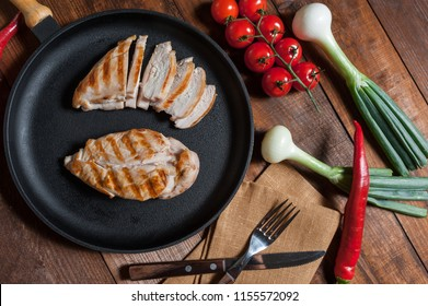 Grilled chiken fillet on frying pan. Raw vegetables in bowl, wooden background