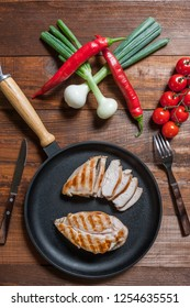 Grilled chiken fillet on frying pan. Raw vegetables in bowl, kitchen background. Flat lay