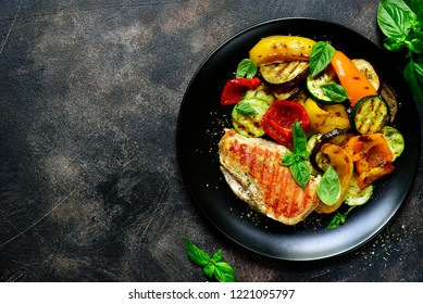 Grilled chiken fillet with vegetables in a black bowl over dark slate, stone or concrete background.Top view with copy space.