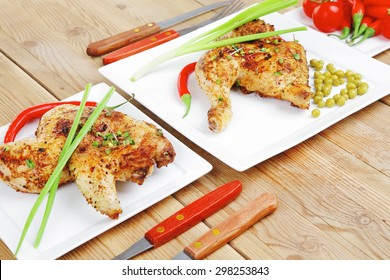 grilled chikens : grilled quarter chicken garnished with green sweet peas , and cutlery on white plates over wooden table