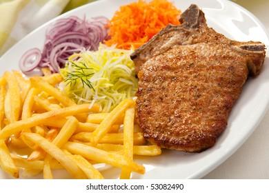 Grilled chop pork, chips and vegetable salad