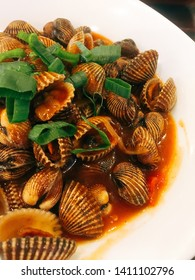 Grilled cockles or clams with a delicious red sauce and chives above it. steamed clams on a white plate. Concept of favorite seafood dishes in Indonesia and Thailand