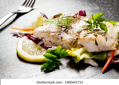 Grilled cod fillet with salad on black slate plate, top view