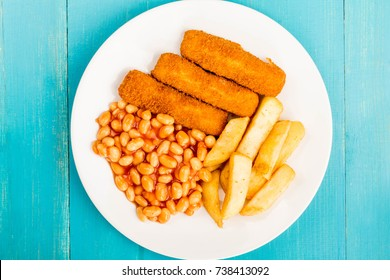 Grilled Cod Fish Fingers With Chunky Chips And Baked Beans in Tomato Sauce On A Blue Wooden Background