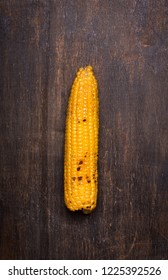 Grilled corn cob on the brown rustic background. Usually served with the BBQ Butter. Vertical orientation