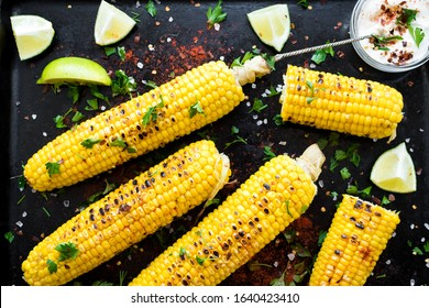 Grilled corn cobs in mexican style with lime, cilantro, chili and white sauce on black background. Top view.