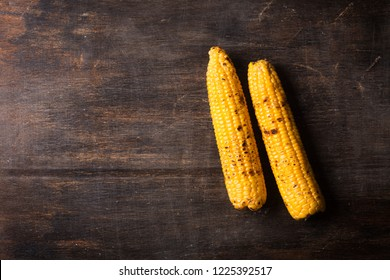 Grilled corn cobs on the brown rustic background with copy space. Usually served with the BBQ Butter or hot sauce