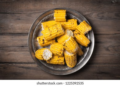 Grilled corn cobs on the brown rustic plate with copy space. Usually served with hot or sweet sauces