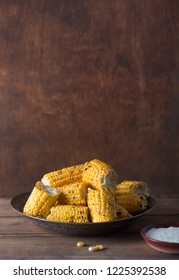 Grilled corn cobs on the brown rustic background with copy space. Served with creamy sauce