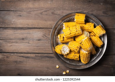Grilled corn cobs on the brown rustic background with copy space. Usually served with the BBQ Butter or Herb Butter