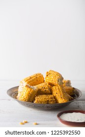 Grilled corn cobs on the old vintage plate with copy space. Usually served with the BBQ Butter or sauces