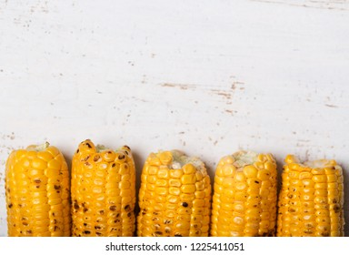 Grilled corn cobs on the white rustic background with copy space. Close up, horizontal orientation