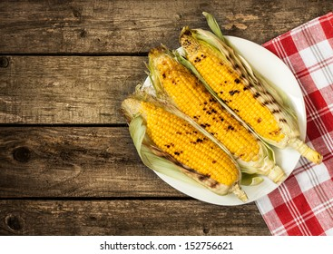 Grilled corn cobs on white plate - vintage wood as background