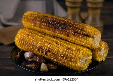 Grilled corn cobs on wooden table