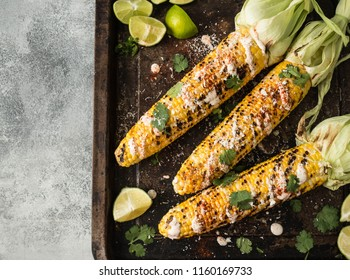 Grilled corn cobs with sauce, coriander, lime, paprika and cheese. Mexican food. Top view. Copy space