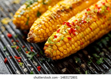 Grilled corn on the cob with butter, herbs, salt and aromatic spices on the grill plate, close-up