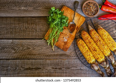 Grilled corn on the cob with herbs on a wooden board on a dark wooden background. Flat lay with copy space.