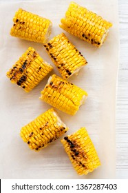 Grilled corn on the cob over white wooden surface, top view. Summer food. From above, overhead, flat lay. Close-up.